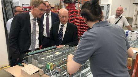 Ministerpräsident Günther (l.) steht an einer Fertigungsstation an der eine Schaltung von einem Mitarbeiter verdrahtet wird.