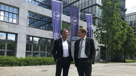 Ministerpräsident Günther (r.) steht mit Bernd Appel vor dem Firmengebäude. Im Hintergrund drei Masten mit Fahnen des Unternehmens.