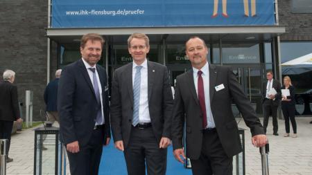 Drei Männer stehen vor dem Eingang eines großen Gebäudes.