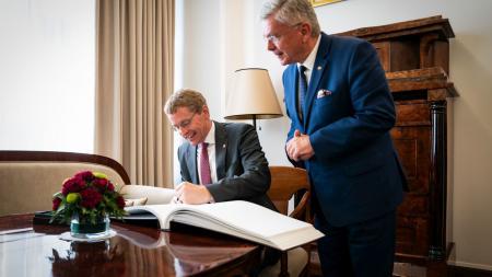 Ministerpräsident Daniel Günther sitzt am Tisch und trägt sich in ein Gästebuch ein. Neben ihm steht der polnische Senatsmarschall Stanislaw Karczewski.