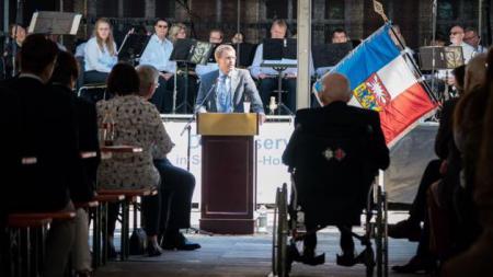Ministerpräsident Daniel Günther steht an einem Rednerpult. Auf einer Bühne hinter ihm ist ein Orchester. Vor ihm sitzen zahlreiche Menschen und ein Mann im Rollstuhl.
