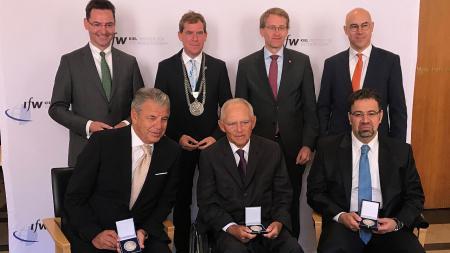 Drei Männer sitzen nebeneinander und halten jeweils eine Medaille in den Händen. Hinter ihnen stehen drei weitere Männer.