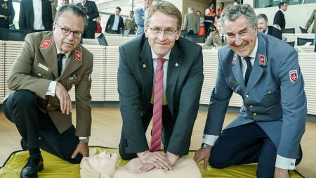 Ministerpräsident Daniel Günther kniet auf dem Boden und drückt mit den Händen auf den Brustkorb einer Puppe. Neben ihm knieen zwei Vertreter der Malteser und Johanniter. Im Hintergrund stehen zahlreiche Menschen im Plenung des Landtags.
