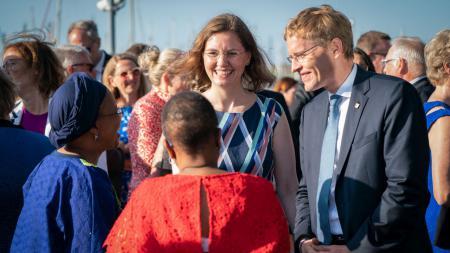 Ministerpräsident Daniel Günther und seine Frau unterhalten sich in einer Menschenmenge mit zwei Frauen.