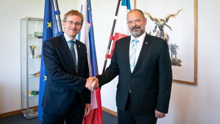 Ministerpräsident Daniel Günther und der slowenische Staatsratspräsident Alojz Kovsca stehen in Günthers Amtszimmer. Hinter ihnen stehen die Flaggen von Schleswig-Holstein, Slowenien und der Europäischen Union.