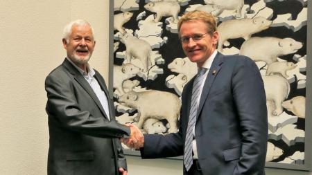 Ministerpräsident Daniel Günther und der Maler Peter Nagel stehen vor einem Bild mit Eisbären und schütteln sich die Hand.