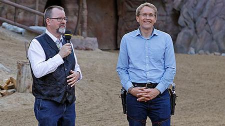 Ministerpräsident Daniel Günther steht auf Sandboden neben einem Mann mit Mikrofon. Günther trägt einen Gürtel mit zwei Revolvern.
