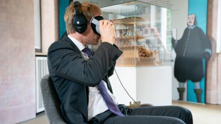 Ministerpräsident Daniel Günther sitzt auf einem Drehstuhl. Er hat Kopfhörer und eine VR-Brille auf.