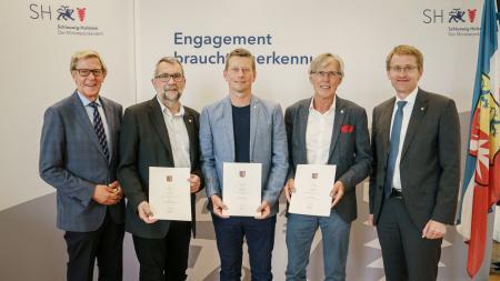 Fünf Männer stehen nebeneinander. Die Drei in der Mitte halten jeweils eine Urkunde in den Händen.