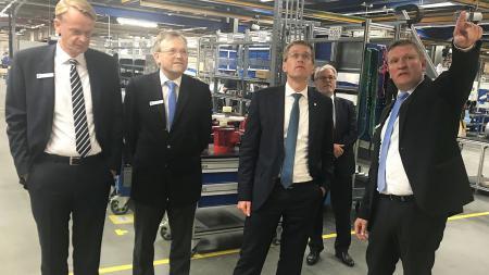 Vier Männer stehen nebeneinander in einer großen Betriebshalle.