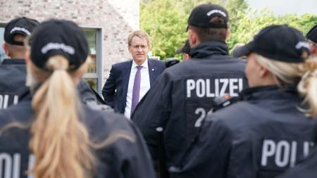 Ministerpräsident Daniel Günther steht vor einer Reihe Polizisten, die man von hinten sieht.