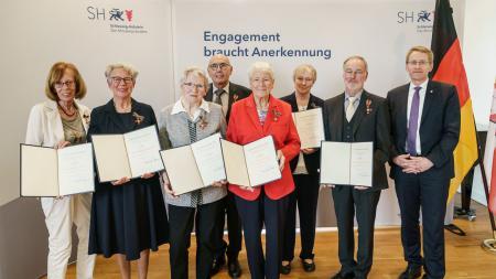 Ministerpräsident Daniel Günther steht neben drei Männern und vier Frauen, die Urkunden in ihren Händen halten.