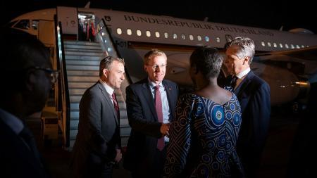 Drei Männer und eine Frau stehen vor einem Flugzeug.