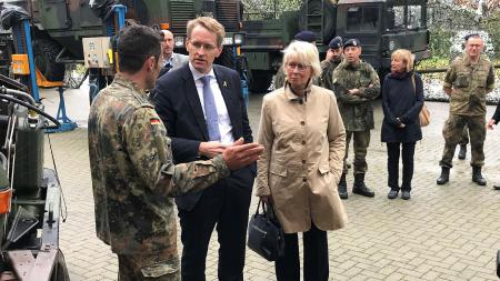 Ein Mann in Anzug und eine Frau im Regenmantel unterhalten sich mit einem Soldaten. Im Hintergrund und an der Seite stehen mehrere Militärfahrzeuge und weitere Menschen.
