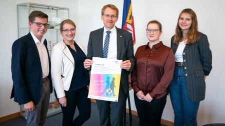 Ein Mann steht mit vier Jugendlichen in einem Raum vor der Flagge Schleswig-Holsteins. Er hält ein Plakat in der Hand, auf dem