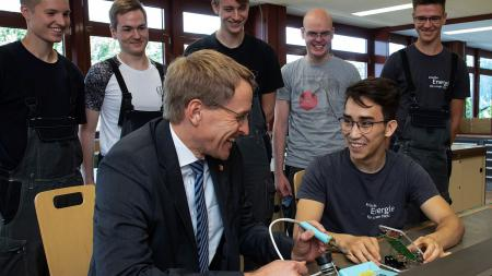 Ein Mann und ein Jugendlicher sitzen an einer Werkbank. Der Mann hat einen Lötkolben in der Hand und lacht. Um die beiden herum stehen mehrere Jugendliche und beobachten sie.