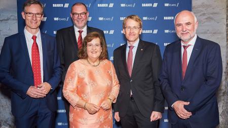 Vier Männer und eine Frau stehen vor einer Plakatwand.