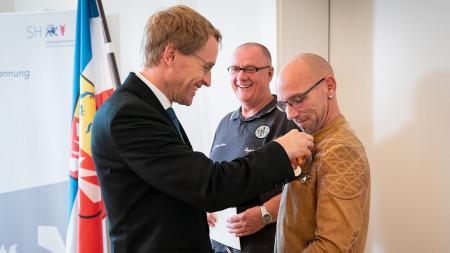 Drei Männer stehen in einem Raum vor einer Flagge. Zwei von ihnen halten eine Urkunde und einen Blumenstrauß in der Hand. An ihrer Kleidung hängt ein Orden.