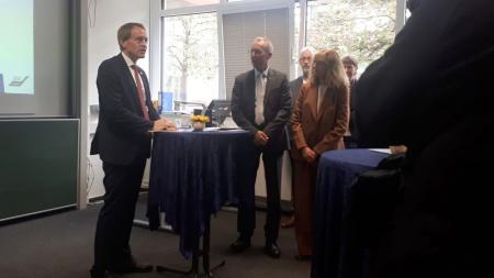 Ein Mann im Anzug steht in einem Raum an einem Stehtisch. Er spricht zu mehreren anderen Menschen im Raum.