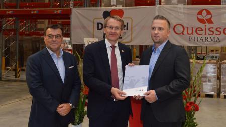 Drei Männer stehen in einer großen Halle mit vielen Industrie-Regalen. Sie halten ein Dokument in den Händen und lächeln in die Kamera.