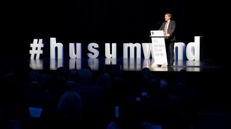 Ein Mann im Anzug steht in einem abgedunkelten Raum auf einer Bühne. Er steht hinter einem Rednerpult und wird von einem Strahler angeleuchtet.