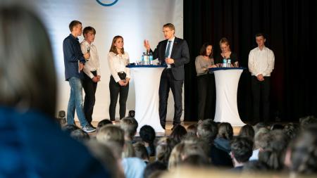 Auf einer Bühne stehen sieben Menschen hinter Stehtischen und diskutieren miteinander. Im Vordergrund sitzen zahlreiche weitere Menschen.