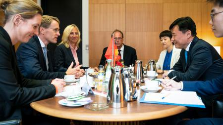 Sieben Menschen sitzen um einem Tisch herum und unterhalten sich. Auf dem Tisch stehen eine deutsche und eine chinesische Flagge.