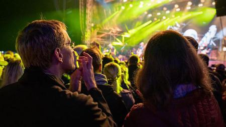 Mehrere Menschen stehen vor einer Bühne und klatschen. Von der Bühne aus strahlt Licht in die Menge.