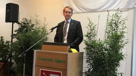 Ein Mann steht hinter einem Rednerpult.