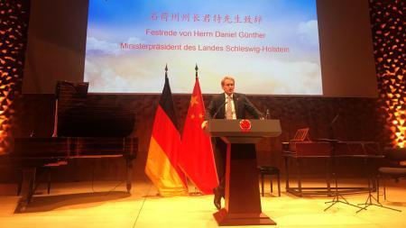 Ein Mann steht auf einem Podium an einem Rednerpult. Im Hintergrund stehen ein Klavier und zwei Flaggen.
