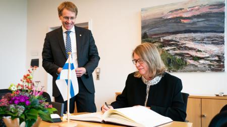 Botschafterin Sipiläinen trägt sich ins Gästebuch der Landesregierung ein, Ministerpräsident Günther schaut ihr dabei über die Schulter.