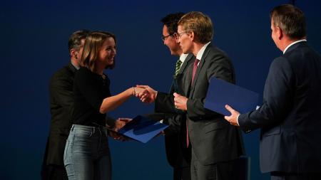 Ein Mann gratuliert einer jungen Frau, beide stehen auf einer Bühne.