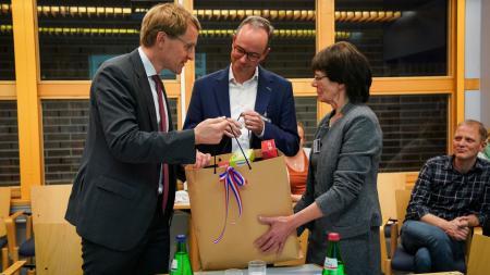 Ein Mann übergibt eine Tüte mit Geschenken an einen Mann und eine Frau.