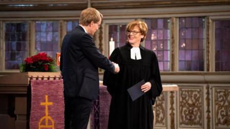 Ein Mann und eine Frau stehen in einer Kirche und schütteln sich die Hände.