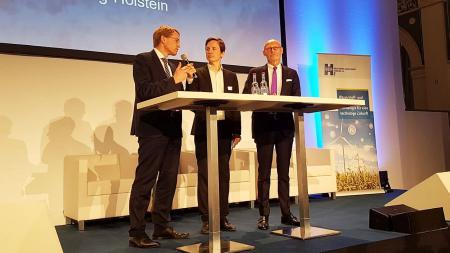 Drei Männer stehen auf einer Bühne und unterhalten sich.