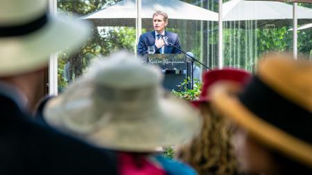 Ein Mann steht hinter einem Rednerpult. Im Vordergrund stehen viele Menschen mit Hüten und hören zu.