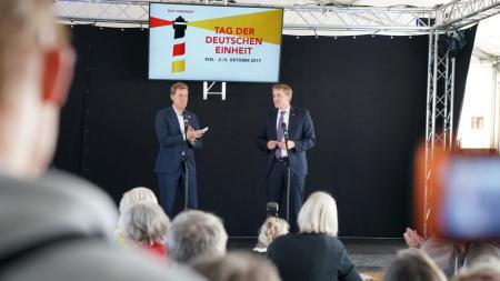 Zwei Männer stehen auf einer Bühne, ein Bildschirm im Hintergrund zeigt das Logo vom Tag der Deutschen Einheit.