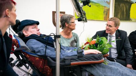 Vier Menschen im Gespräch, ein Mann sitzt im Rollstuhl.