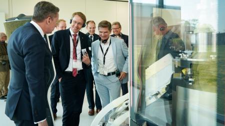 Drei Männer stehen vor einer Maschine und sprechen miteinander.