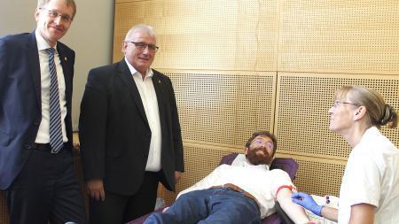 Zwei Männer stehen neben einer Liege, auf der ein Mann gerade für die Blutspende vorbereitet wird.