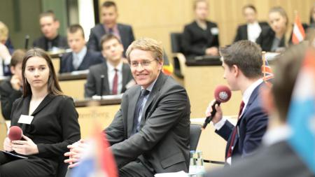 Ein Mann diskutiert mit Jugendlichen in einem Plenum.