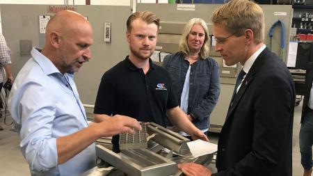 Drei Männer stehen um eine Maschine herum. Sie schauen sich daraufliegende, metallische Objekte an.