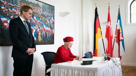 Eine Frau sitzt an einem Tisch und schreibt etwas in ein Buch. Ein Mann steht neben ihr und schaut dabei zu. Im Hintergrund stehen die Flaggen Dänemarks, Deutschlands und Schleswig-Holsteins in einem Ständer.