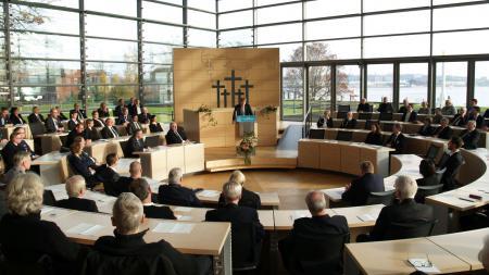 Ein Mann steht in einem Parlamentssaal an einem Redepult und spricht.