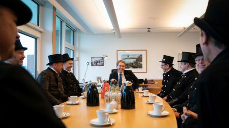 Acht Schornsteinfeger sitzen gemeinsam mit Ministerpräsident Daniel Günther am Tisch.