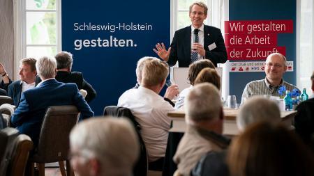 Ein Mann steht an einem Rednerpult und spricht zu einer Gruppe Menschen vor ihm.