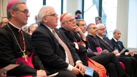 Viele Männer sitzen in einer Reihe und lauschen einem Redner