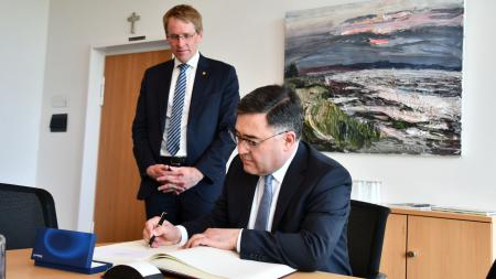 Ein Mann sitzt an einem Tisch und unterschreibt ein Dokument. Ein zweiter Mann steht neben ihm.