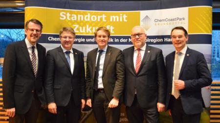 Fünf Männer stehen nebeneinander und lächeln in die Kamera.