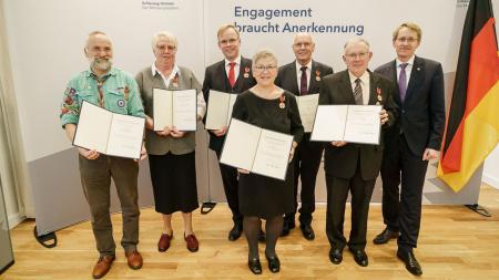 Sieben Menschen stehen nebeneinander und lächeln in die Kamera. Sechs von ihnen halten Urkunden in den Händen.